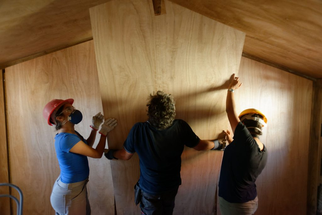 three people fitting timber panelling