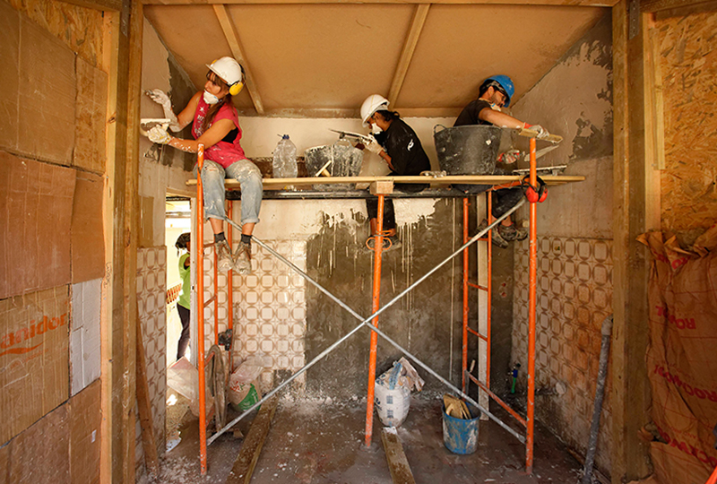 three students on a construction platform