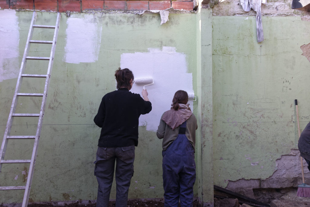 girls painting food forest wall